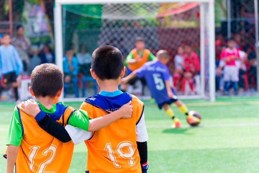 Niños jugando a futbol en equipo
