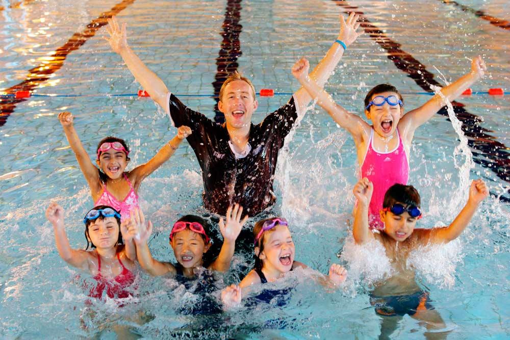 Niños practicado natación con su entrenador