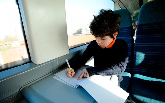 Niño escribiendo en su diario de viaje