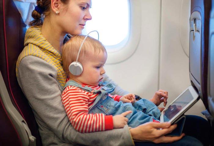 Madre con su bebé e ipad en el avión