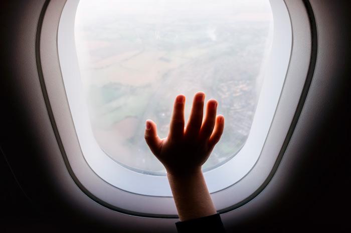 Ventana de avión con la mano de un niño