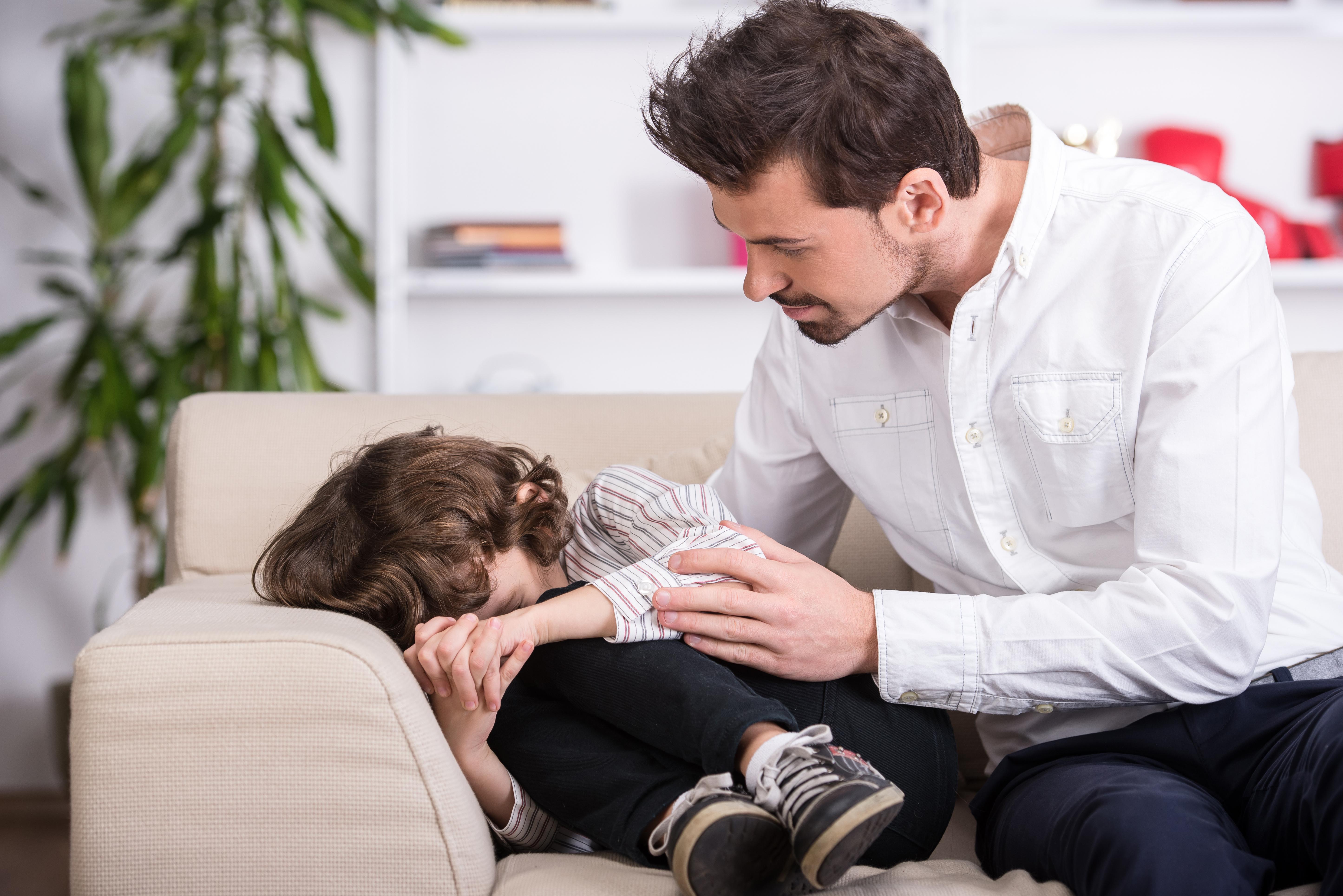 Niño llorando y padre consolándolo